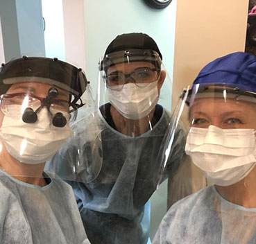 The David Paulussen, DMD team wearing their PPE of surgical masks and face shields